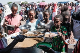 Ethiopian refugees who fled the Tigray conflict receive food at the Border Reception Centre in Hamdayet, eastern Sudan [Yasuyoshi Chiba/AFP]