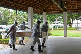 Municipal workers carry the coffin of an unclaimed body of a COVID-19 victim to a crematorium in Colombo in this December 10 photo [Lakruwan Wanniarachchi/AFP]