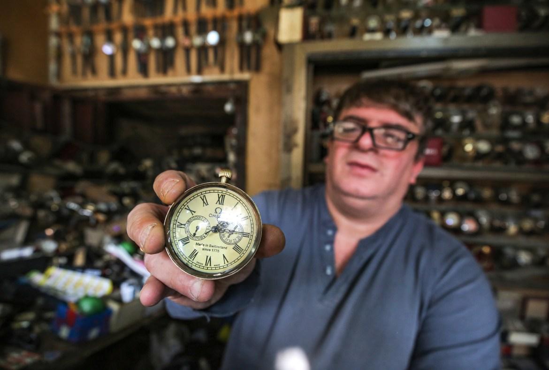 Youssef Abdelkarim presents an antique Omega pocket watch as he sits at his workshop. [Ahmad Al-Rubaye/AFP]