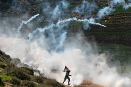 Palestinian protesters run for cover from tear gas canisters fired by Israeli forces during a demonstration against the expansion of illegal settlements near the occupied West Bank village of Beit Dajan, east of Nablus [Jaafar Ashtiyeh/AFP]