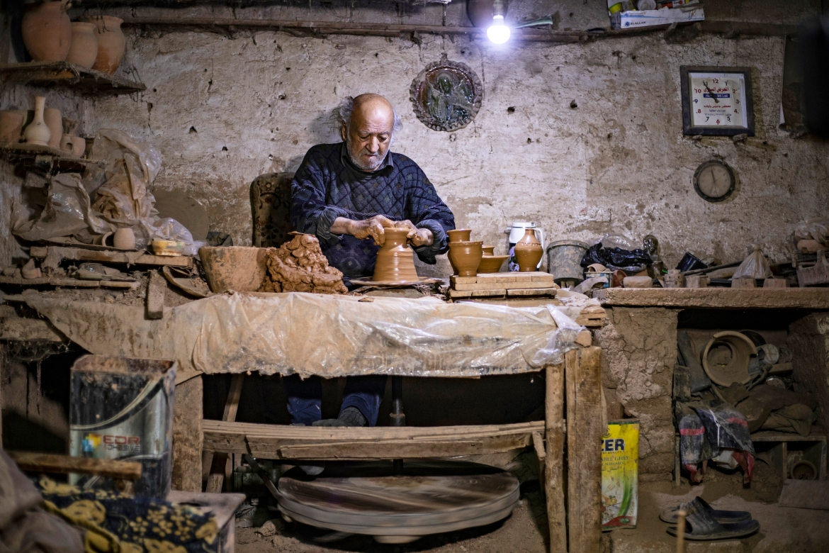 Petros was a teenager when he had to take over from his sick father and become the main potter in the family. [Delil Souleiman/AFP]