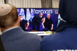 Israeli Prime Minister Benjamin Netanyahu, right, and Health Minister Yuli Edelstein, left, are injected with the Pfizer-BioNTech vaccine live on TV at the Sheba Medical Center, the country's largest hospital, in Ramat Gan near the coastal city of Tel Aviv, on December 19, 2020 [Jack Guez/AFP]