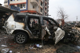 A damaged vehicle is seen at the site of a car bomb attack in Kabul on December 20, 2020 [Zakeria Hashimi/AFP]
