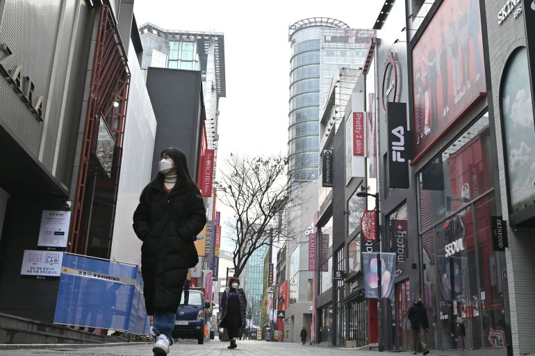 Masked pedestrians walk through the quiet Myeong-dong shopping district in Seoul on December 23, 2020 as South Korea banned gatherings of more than four people in the capital and surrounding areas [Jung Yeon-je / AFP]