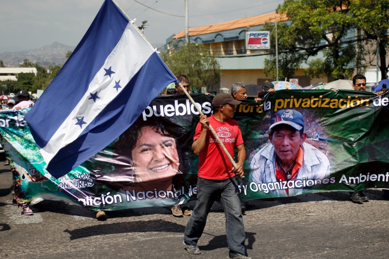 An Indigenous man holds a Honduran national flag during a march to demand justice for slain environmental rights activist Berta Caceres in Tegucigalpa in 2016 [File: Jorge Cabrera/Reuters]