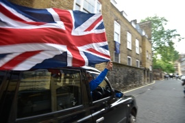 June 24, 2016: A taxi driver holds a Union flag, as he celebrates following the result of the EU referendum, in central London. [Toby Melville/Reuters]
