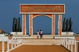 A couple are seen walking away from the monument of 'Point of No Return' at the historic slave port of Ouidah, Benin, July 18, 2019. The 400-year anniversary of the first slave boat to arrive in America from Africa has caused a rush of interest in heritage tourism in West Africa, as descendants of slaves from America, the Caribbean and Europe visit ancient sites to delve into a dark and often hidden past. Picture taken July 18, 2019. REUTERS/Afolabi Sotunde