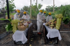 Officials in personal protective equipment (PPE) prepare for the cremation of two people who died from COVID-19 in Bali in October [Nyoman Hendra Wibowo/Antara Foto via Reuters]