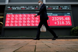 A man walks past a stock quotation board outside a brokerage in Tokyo, Japan [File: Issei Kato/Reuters]