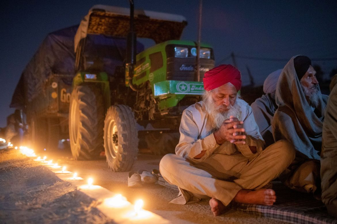 A farmer prays to mark the 551st birth anniversary of Guru Nanak Dev, the first Sikh guru and founder of the Sikh faith, during a protest against the newly passed farm bills at Singhu border near Delhi. [Danish Siddiqui/Reuters]