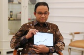 Anies Baswedan shows a chart during an interview at his office amid the coronavirus disease (COVID-19) outbreak in Jakarta, Indonesia, September 17, 2020 [File: Yuddy Cahya Budiman/ Reuters]