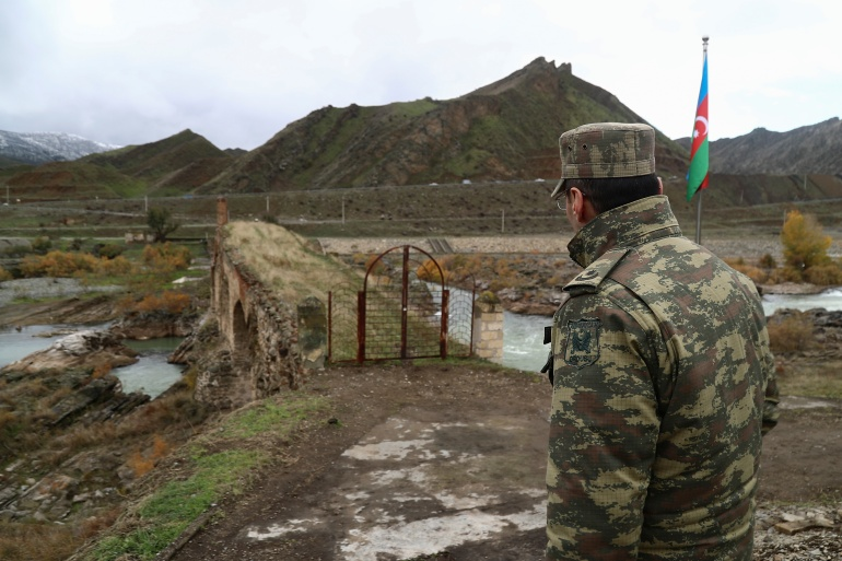 An Azeri service member looks at the ancient Khodaafarin Bridge near the border with Iran in the area, which came under the control of Azerbaijan's troops following a military conflict over Nagorno-Karabakh against ethnic Armenian forces and a further signing of a ceasefire deal in Jabrayil district [Aziz Karimov/Reuters]
