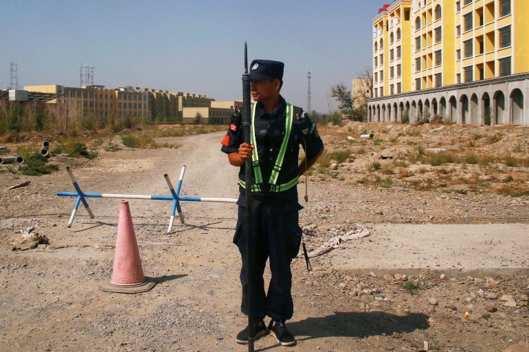 A Chinese police officer standing near what is officially called a 'vocational education centre' in Yining, Xinjiang Uighur Autonomous Region, September 4, 2018 [File: Thomas Peter/Reuters]