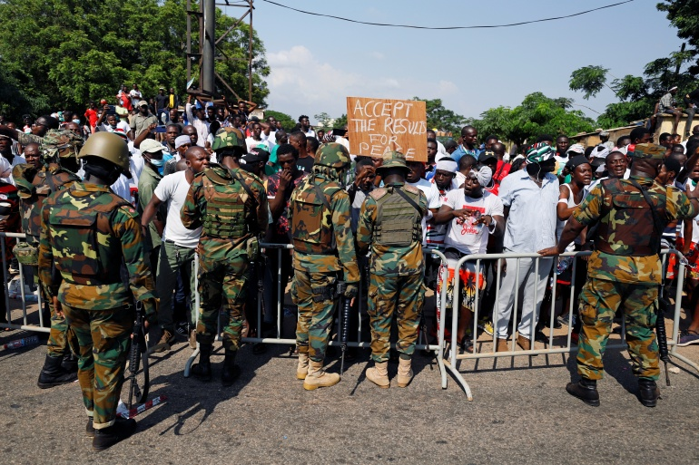 Soldiers stand as supporters of the opposition party, the National Democratic Congress (NDC), protest outside Ghana's electoral commission ahead of official results in Accra on Wednesday [Francis Kokoroko/Reuters]