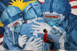 A doctor collects a swab sample for coronavirus outside a clinic in Shah Alam in Malaysia [Lim Huey Teng/Reuters]
