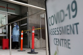 A nurse guides people being tested for COVID-19 outside a hospital in Toronto on December 10, 2020 [Chris Helgren/Reuters]