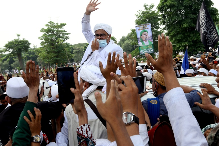 Rizieq Shihab, the leader of Indonesian Islamic Defenders Front, greets supporters in November after arriving back in the country from self-exile [File: Antara Foto/Muhammad Iqbal/Reuters]