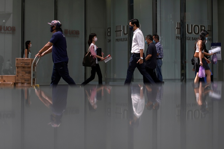 People wearing protective masks as a precaution against COVID-19 walk during lunch hour at the central business district in Singapore, December 14, 2020 [Edgar Su/ Reuters]