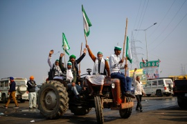 Farmers shout slogans as they sit on a tractor during a protest against farm bills passed by India's parliament, at the Delhi-Uttar Pradesh border in Ghaziabad [Adnan Abidi/Reuters]