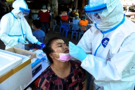 A medical worker performs a nose swab on a migrant worker at a seafood market amid the COVID-19 outbreak, in Samut Sakhon province, Thailand, December 19, 2020 [Panumas Sanguanwong/Reuters]