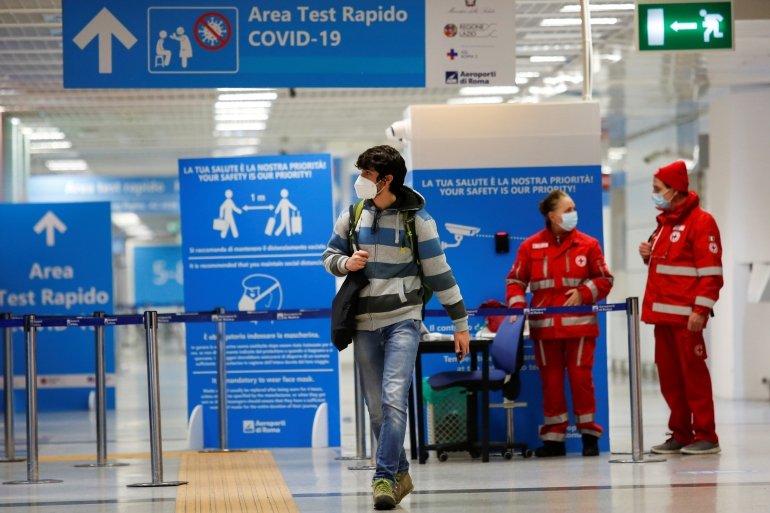 A passenger walks at Fiumicino airport in Rome after the Italian government announced all flights to and from the UK will be suspended over fears of a new strain of the coronavirus [Remo Casilli/Reuters]