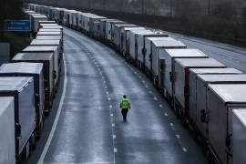 A man walks past lorries parked on the M20 motorway after EU countries imposed a ban on travel from the UK [Simon Dawson/Reuters]