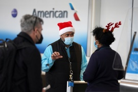 A passenger approaches two airline workers in Christmas-themed headwear at Ronald Reagan Washington National Airport, in Arlington, Virginia, US, December 22, 2020 [Kevin Lamarque/ Reuters]