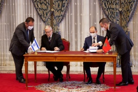 Unidentified Moroccan and Israeli officials sign memorandums of understanding during a visit by Israeli envoys to Rabat [Shereen Talaat/Reuters]