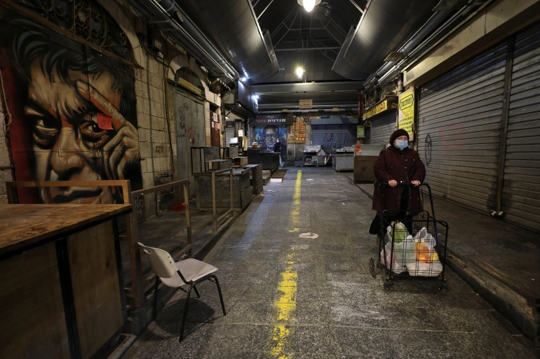 A woman walks past closed stores as Israel imposes a third national lockdown to fight climbing coronavirus disease (COVID-19) infections, in Jerusalem December 27, 2020 [Ammar Awad/Reuters]