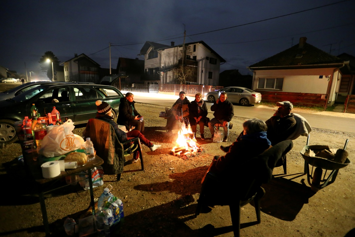 People warm up around a fire after the earthquake in Petrinja. [Antonio Bronic/Reuters]