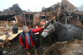 Farmer Tomislav Suknaic touches his horse in front of his damaged household in Majske Poljan village after an earthquake in Croatia [Antonio Bronic/Reuters]