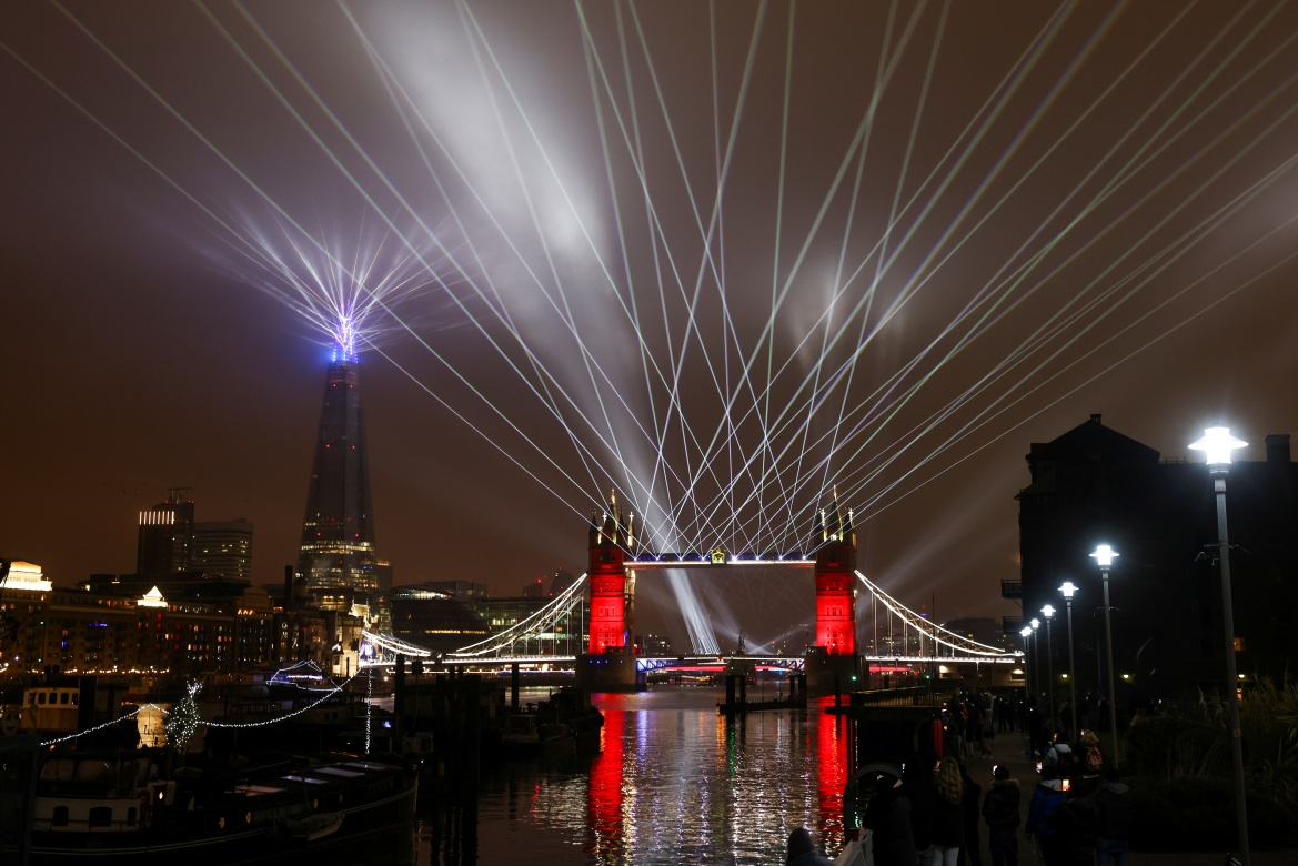 A light show over London's Tower Bridge as the British capital welcomed a new year without the usual crowds of revellers [Simon Dawson/Reuters]