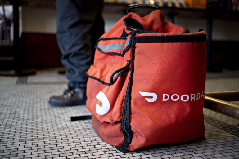 As Americans sat at home and ordered meals in from restaurants, DoorDash climbed in the US food delivery app market [File: Andrew Harrer/Bloomberg]