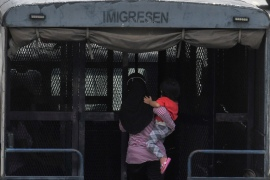 A woman carries her child onto an Immigration Department truck during a raid in Kajang, near Kuala Lumpur, last month [Hasnoor Hussain/Al Jazeera]