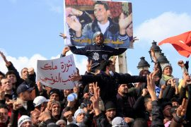 Tunisian protesters demonstrate beneath a poster of Mohamed Bouazizi, a street vendor who set himself on fire to protest against social conditions, starting the Arab Spring in late 2010 [File: Salah Habibi/AP]