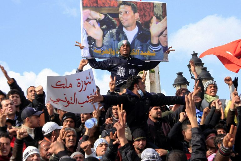 In a photo from January 2011, Tunisian protesters demonstrate beneath a poster of Mohamed Bouazizi, near the prime minister's office in Tunis [File:Salah Habibi/AP Photo]