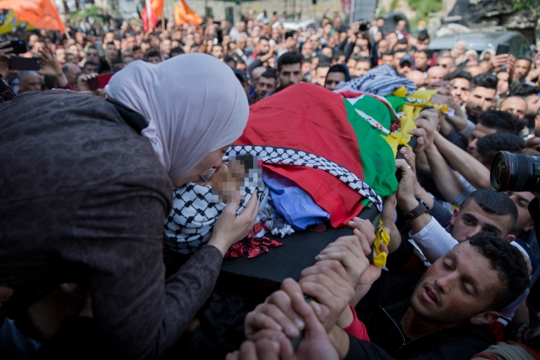 Wafa Manasra, the mother of Palestinian Ahmad Manasra, kisses him goodbye at his funeral in the West Bank village of Wad Fokin, near Bethlehem [Nasser Nasser/AP Photo]