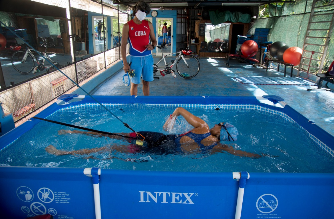 Leslie Amat, a Cuban triathlete, swims in a pool with straps that keep her from advancing, under the watch of her trainer Diosele Fernandez on the patio of her home in Havana, Cuba, in April 2020. [Ismael Francisco/AP Photo]