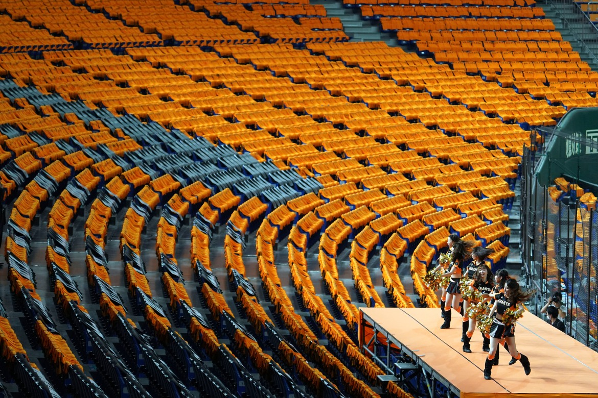 Cheerleaders perform to empty stands before the start of a baseball game between the Yomiuri Giants and the Hanshin Tigers in Tokyo in June. [Eugene Hoshiko/AP Photo]