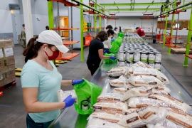 Volunteers load non perishable foods in green grocery bags for a school student food programme at the Houston Food Bank in Houston, US on October 14, 2020 [File: AP/Michael Wyke]