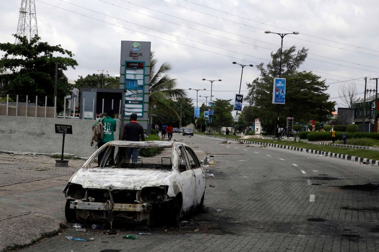 A burnt-out car is seen on Lekki Road in Lagos on October 23, 2020 [File: Sunday Alamba/AP]
