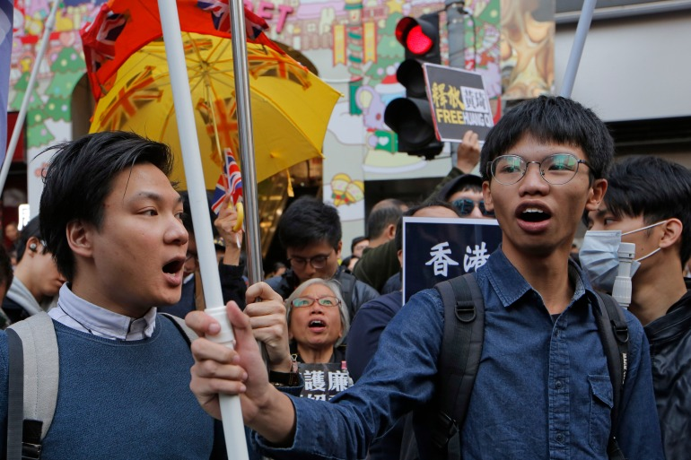 Tony Chung, right, marches during an annual New Year protest in Hong Kong. The former leader of the Hong Kong pro-independence student group Studentlocalism has been jailed for four months for 'insulting' the Chinese flag [File: Kin Cheung/AP Photo]