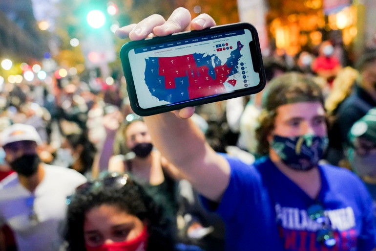 A supporter of President-elect Joe Biden holds up his mobile phone to display the electoral college map after the 2020 Presidential Election is called, November 7, 2020, in Philadelphia [John Minchillo/AP Photo]