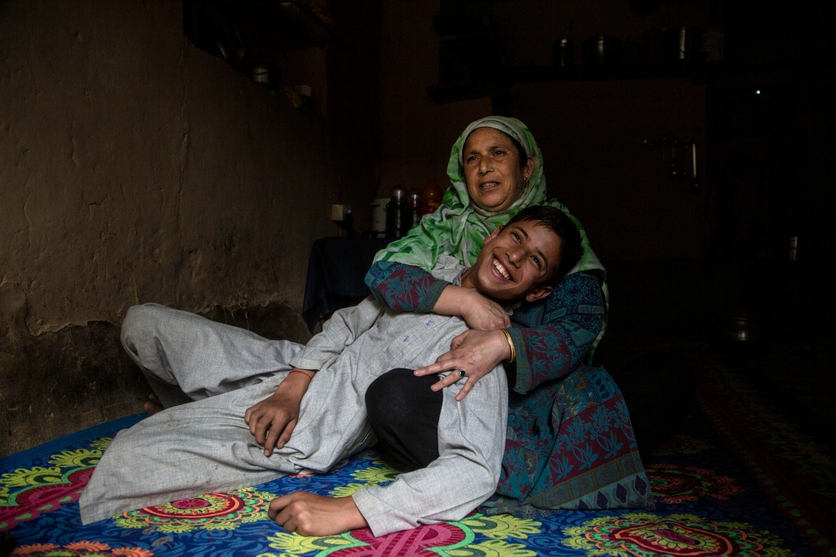 "Zamrooda with her son Sahil Majeed, who she saved from a leopard attack in 2009 in Srinagar. ""I had finished almost all work at my home. I was supposed to go in fields for work. I saw something strange, an animal jumped on me and I was not able to move. I was bleeding and he tore my clothes when suddenly it comes to my mind that my son was outside. I ran away towards my son and I hit leopard's mouth with a stick and pulled my son out from his mouth ... My son was four years old that time."" [Mukhtar Khan/AP Photo]"