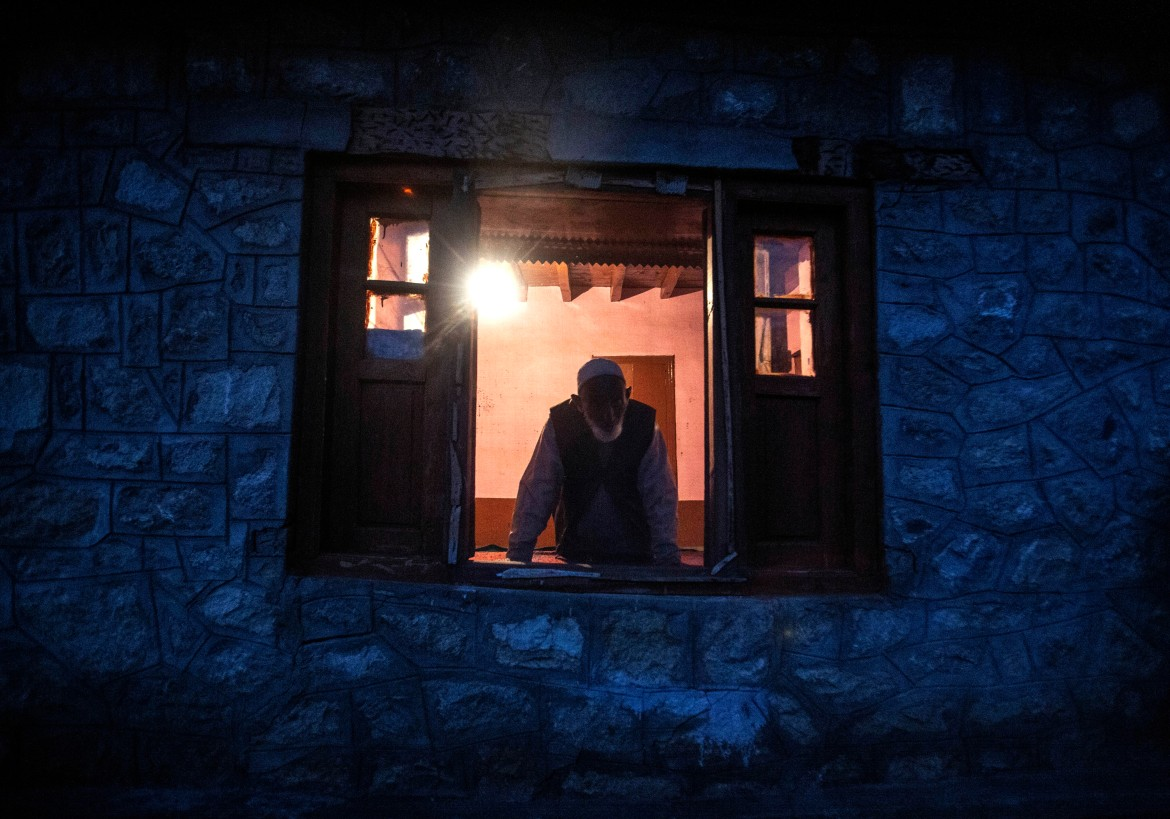 Lal Din, an elderly Kashmiri villager, looks out from a window of his home at Dardkhor village, an area that experiences frequent attacks by wild animals, on the outskirts of Srinagar. [Mukhtar Khan/AP Photo]