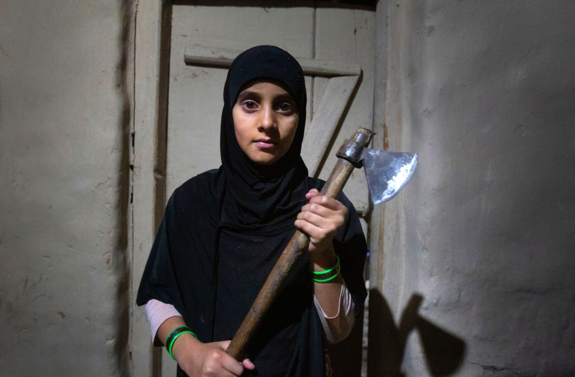 Muskan, 14, shows an axe that her family carries when they go outdoors at night to protect themselves from wild animals, at Dardkhor village, outskirts of Srinagar. [Mukhtar Khan/AP Photo]