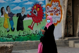 A woman walks past a mural encouraging the wearing of face masks amid the coronavirus pandemic in Nusseirat refugee camp, central Gaza Strip [Adel Hana/AP]