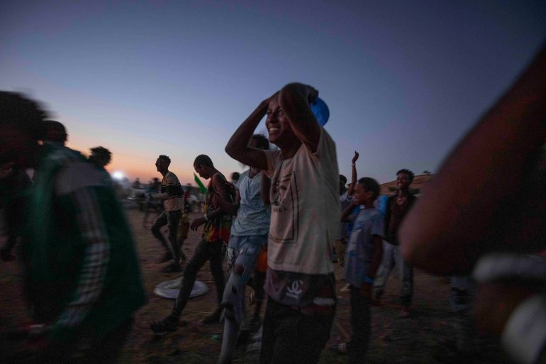 Tigray men who fled the conflict in Ethiopia's Tigray region, run to receive cooked rice from charity organisation Muslim Aid, at Umm Rakouba refugee camp in Gadarif, eastern Sudan on November 27, 2020 [File: Nariman el-Mofty/AP Photo]