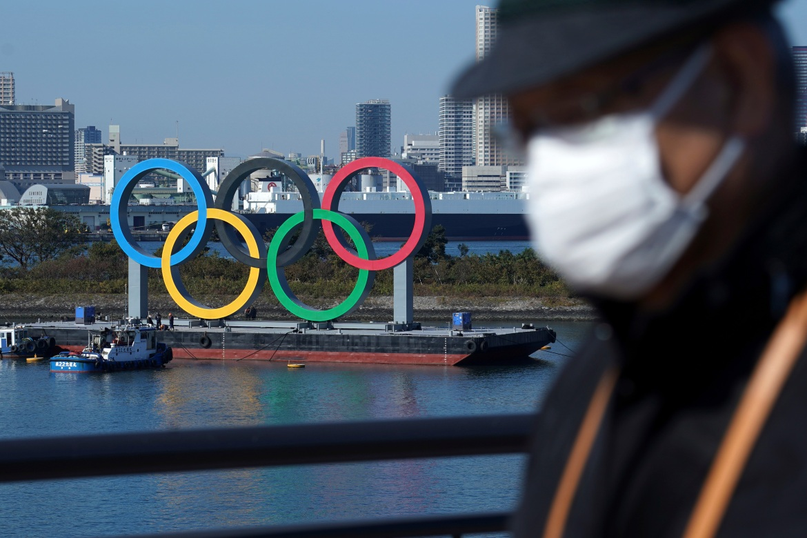 A man wearing a protective face mask walks past the Olympic rings on Tuesday, December 1, 2020, in Tokyo. The five Olympic rings are back in Tokyo Bay after they were removed for maintenance four months ago, shortly after the Tokyo Olympics were postponed until next year because of the COVID-19 pandemic. [Eugene Hoshiko/AP Photo]