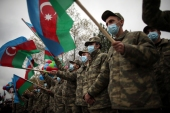 Azerbaijani soldiers hold national flags as they celebrate the transfer of the Lachin region to Azerbaijan's control, as part of a peace deal that required Armenian forces to cede the Azerbaijani territories they held outside Nagorno-Karabakh [Emrah Gurel/AP]